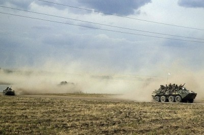 Servicemen sit atop an armoured vehicle as they travel through the steppe near the village of Krasnodarovka in Rostov region