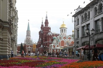 People walk past flowers located near GUM department store, Red Square and the Kremlin in Moscow