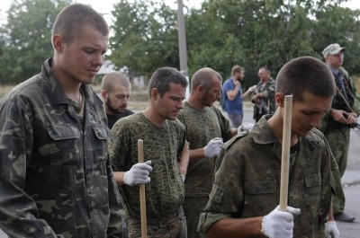 Prisoners-of-war, who are Ukrainian servicemen captured by pro-Russian separatists, gather as they are assigned to clean a street in Snizhne (Snezhnoye), Donetsk region