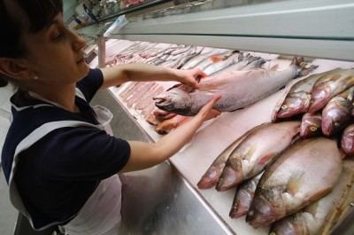 A vendor sells Norwegian fish at the city market in St.Petersburg